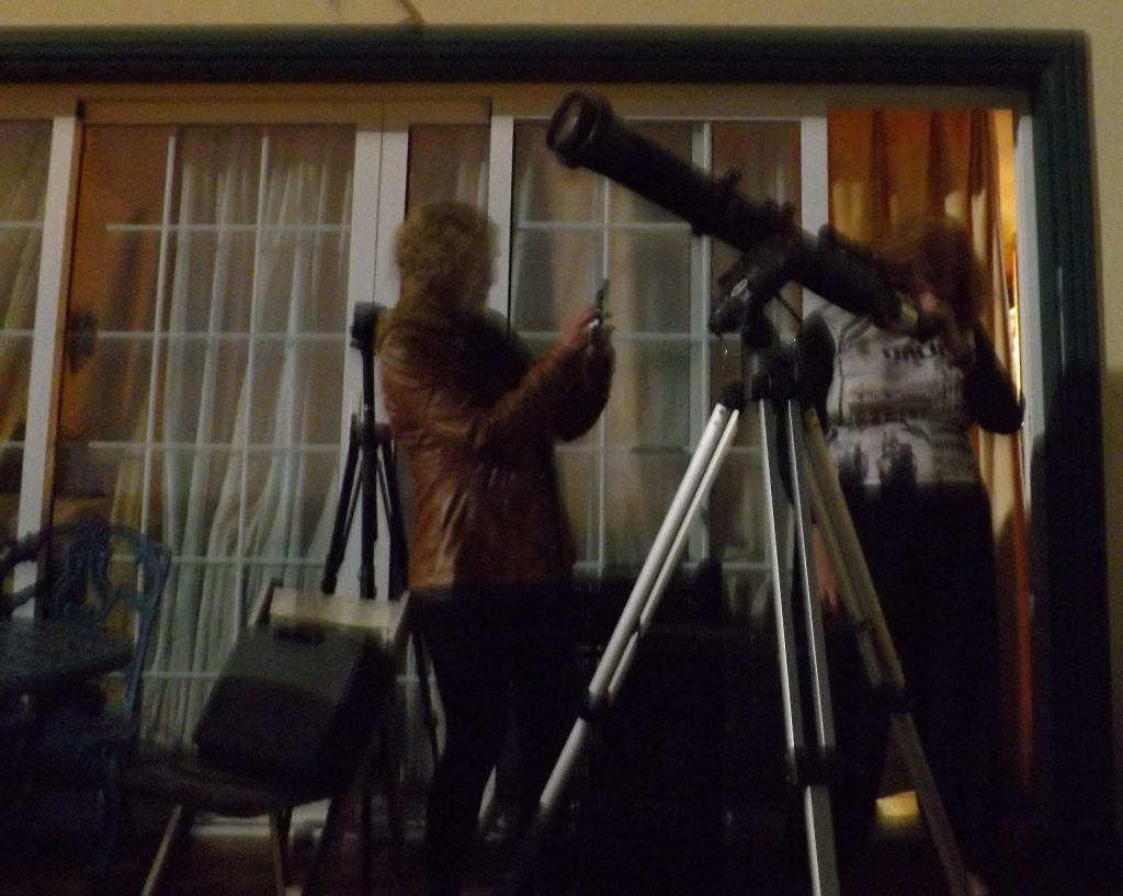 10 cm telescope on a tripod with two people