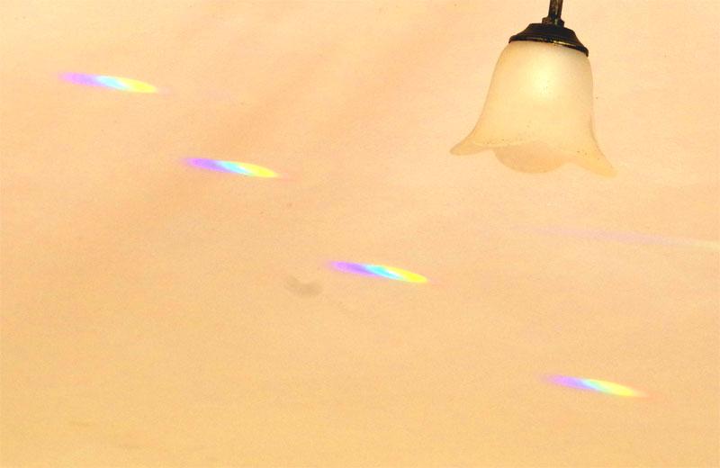Three small rainbows near a light fitting